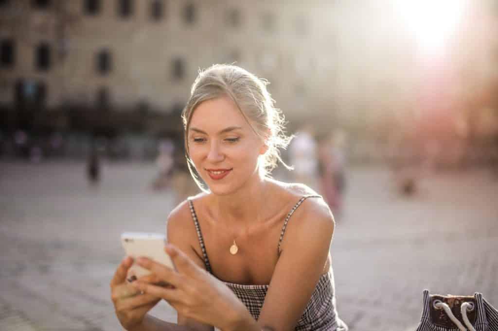Femme souriante regardant son téléphone